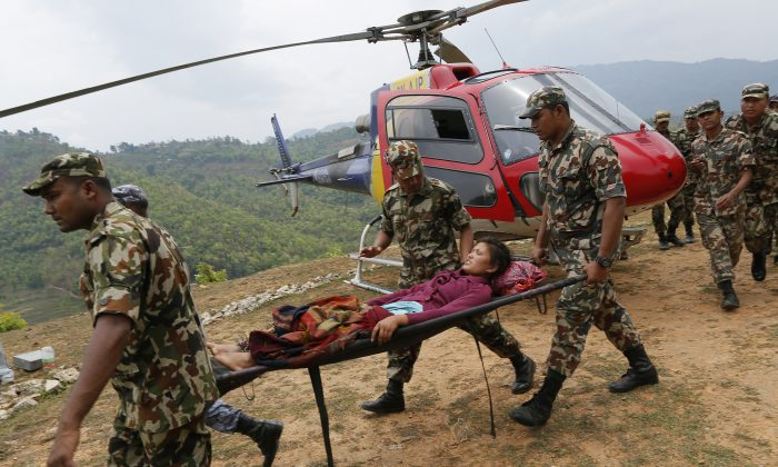 Sita Karka, suffering two broken legs from Saturday's massive earthquake, arrives by helicopter from the heavily-damaged Ranachour village at a landing zone in the town of Gorkha, Nepal, Tuesday, April 28, 2015. (AP/Wally Santana)