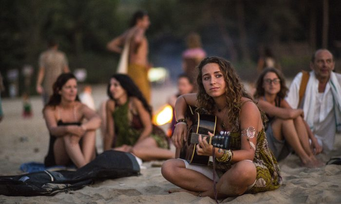 As the sunsets a woman plays guitar as people behind her gather around a bond fire on the Gokarna beach in India. (Jedraszak/iStock)