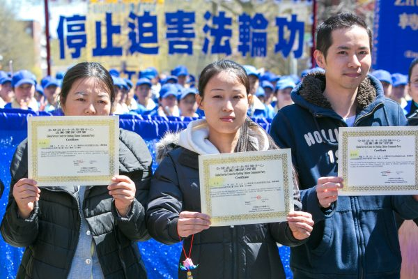 People from mainland China hold certificates they received after quitting the Chinese Communist Party during parade in Flushing, New York, on April 25, 2015, calling for an end to the persecution of Falun Gong in China and celebrating 200 million people who have quit the Chinese Communist Party since 2004. (Benjamin Chasteen/Epoch Times)