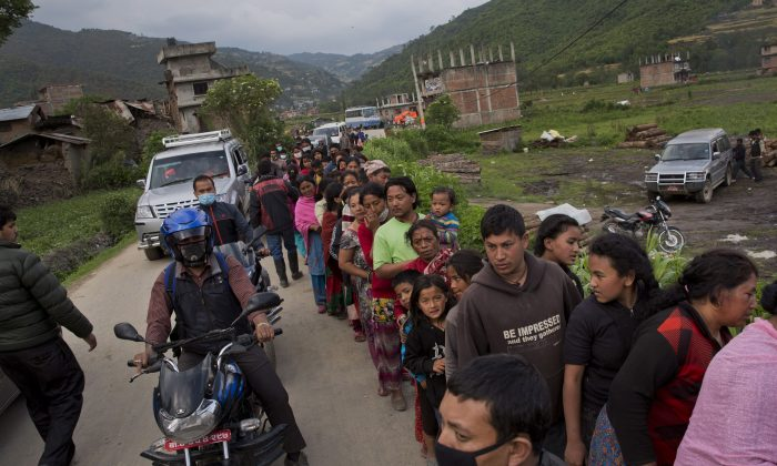 Nepalese villagers stand in a queue to receive food being distributed on the outskirts of Kathmandu on April 29, 2015. The massive earthquake that shook Nepal's capital and the densely populated Kathmandu Valley has left hundreds of thousands living in the open without clean water or sanitation. (AP Photo/Bernat Amangue)