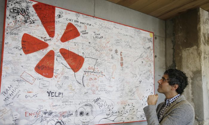 In this photo taken Friday, Aug. 1, 2014, Yelp CEO Jeremy Stoppelman looks over a wall signed by visiting employees from other cities at his company's headquarters in San Francisco. (AP Photo/Eric Risberg)
