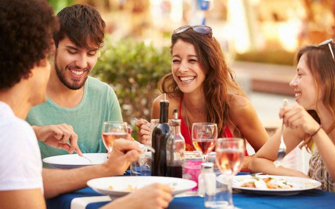 Group of young friends enjoying meal in outdoor restaurant via Shutterstock*