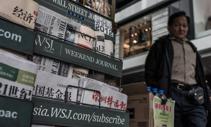 A man walks past a newspaper kiosk in Hong Kong on Jan. 12, 2015. (Philippe Lopez/AFP/Getty Images)