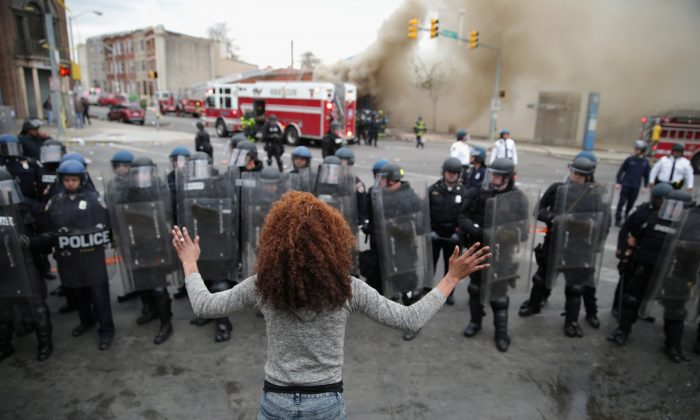 A woman faces down a line of Baltimore Police officers in riot gear during violent protests following the funeral of Freddie Gray April 27, 2015 in Baltimore, Maryland. (Chip Somodevilla/Getty Images)