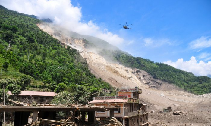 A Nepalese Army helicopter flies over the site of a landslide during a rescue operation in Sindhupalchowk area, about 120 kilometers (75 miles) east of Katmandu, Nepal, Saturday, Aug. 2, 2014. (AP Photo/Dinesh Gole)