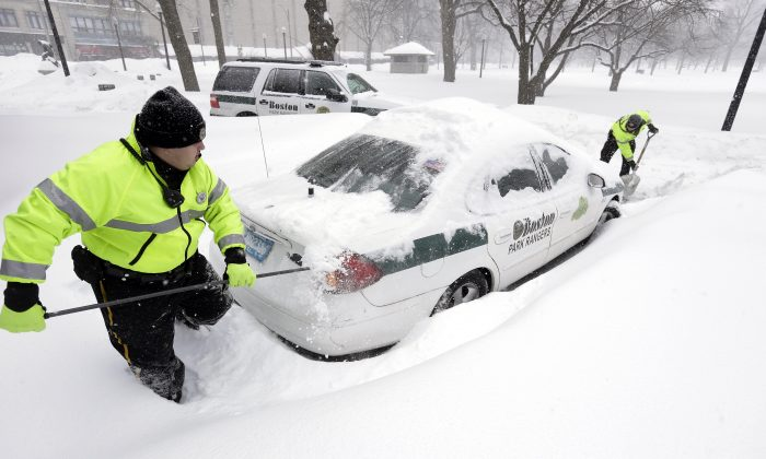 Boston park rangers clear snow from around their car in Boston, on Feb. 9, 2015. (AP Photo/Steven Senne)