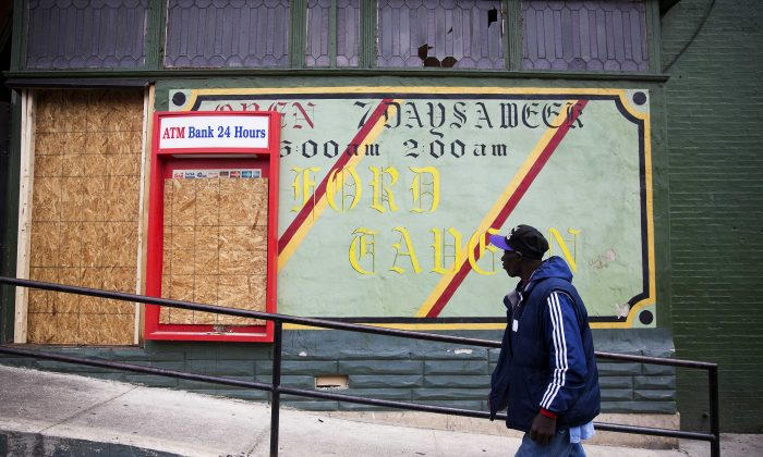 A man walks past the damaged Oxford Tavern in Baltimore. In a presidential campaign where candidates are jockeying to be champions of the middle class and courting donations from the wealthy, the poor are inching their way into the debate.  (AP Photo/David Goldman)