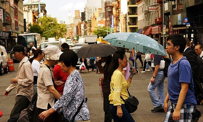 People walk through New York's Chinatown district on July 11, 2014 in New York City. (Spencer Platt/Getty Images)