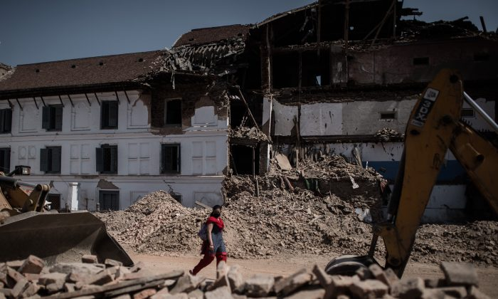A woman walks past debris-strewn historical heritage site Durbar Square in Kathmandu on May 3, following a magnitude-7.8 earthquake, which struck the Himalayan nation on April 25. The death toll in Nepal from the devastating earthquake has risen to 7,040, an official from the National Emergency Operations Centre said on May 3. (Philippe Lopez/AFP/Getty Images)