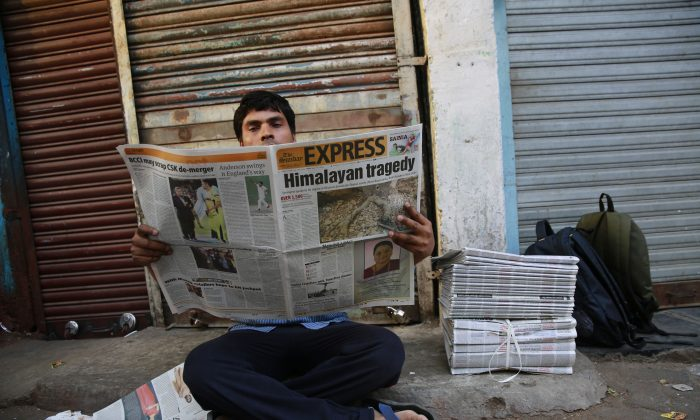 An Indian man reads a newspaper with front-page news of Nepal earthquake  in Mumbai, India, on April 26, 2015. (AP Photo/Rafiq Maqbool)