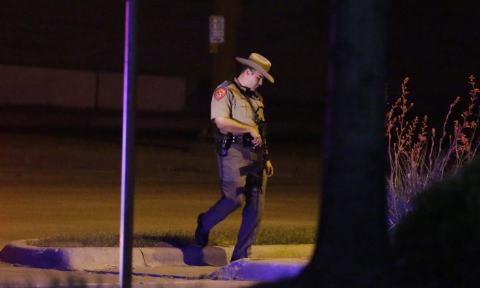 A Texas state trooper stands guard at a parking lot near the Curtis Culwell Center where a provocative contest for cartoon depictions of the Prophet Muhammad was held Sunday, May 3, 2015, in Garland, Texas. (AP Photo/LM Otero)