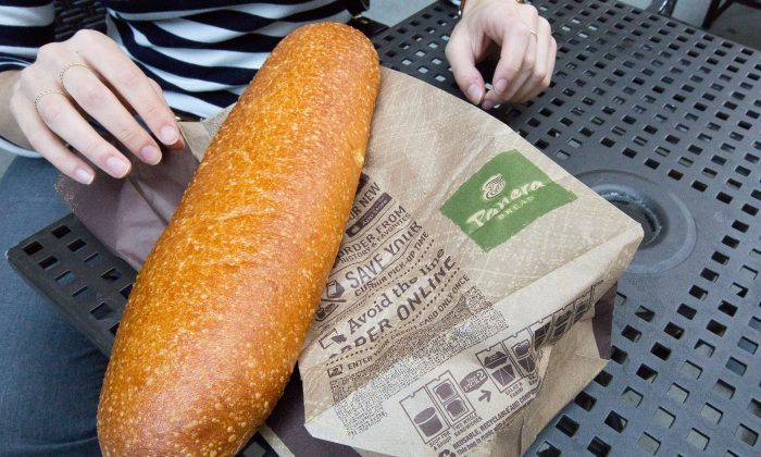 A customer with a bread purchased at a Panera Bread store in Chelsea, Manhattan, on May 5, 2015. (Petr Svab/Epoch Times)
