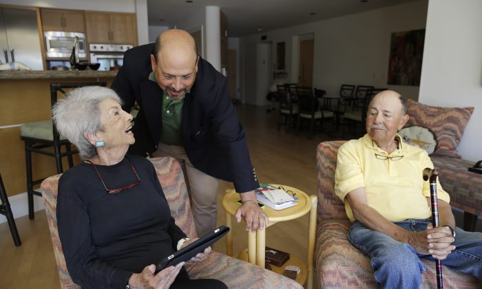 Phil Dworsky visits with his parents, Dorothy and Bill Dworsky, at their home in San Francisco. Each time an elder Dworksy opens the refrigerator, closes the bathroom door or lifts the lid on a pill container, tiny sensors in their home make notes on a digital logbook, which the younger Dworsky monitors daily on his smartphone. (AP/Eric Risberg)