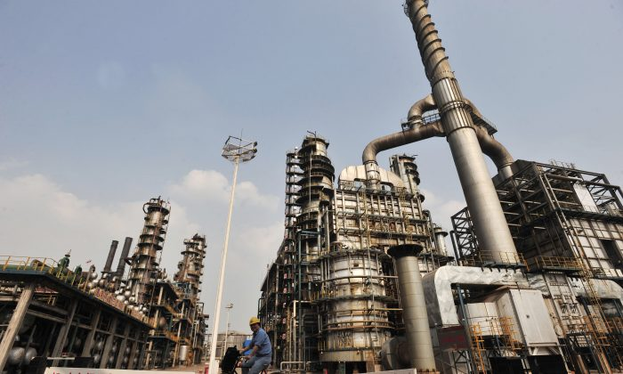 A worker rides a bicycle at an oil refinery of China's Sinopec, in Wuhan, central China's Hubei Province on May 10, 2011. (STR/AFP/Getty Images)