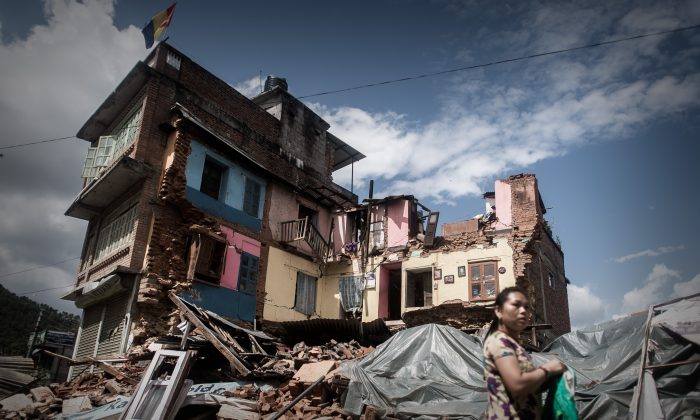 A woman walks past a destroyed house in Chautara, Nepal on April 30, 2015. Last week, aide workers rescued 4 men trapped under rubble in Chautara using radar technology. (PHILIPPE LOPEZ/AFP/Getty Images)