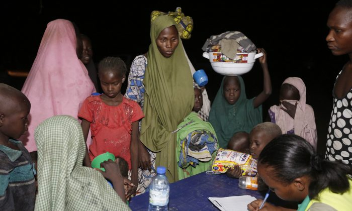 Women and children who were rescued by Nigerian soldiers from Boko Haram extremists at Sambisa Forest register their names upon their arrival at a refugee camp in Yola, Nigeria, Saturday May 2, 2015. They were among a group of 275 people rescued from the Islamic extremists, the first to arrive at the refugee camp Saturday after a three-day journey to safety. Nigerian military said it has rescued more than 677 girls and women and destroyed more than a dozen insurgent camps in the past week. (AP Photo/Sunday Alamba)