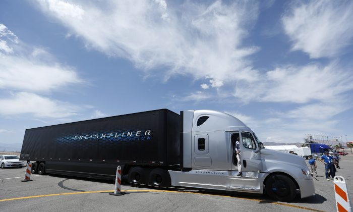 People exit Daimler's Freightliner Inspiration self-driving truck after a demonstration Wednesday, May 6, 2015, in Las Vegas. (AP Photo/John Locher)