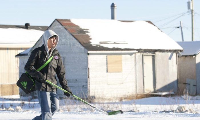 A youth carrying a hockey stick walks past a boarded-up house in Attawapiskat, Ont., Nov. 29, 2011. Crime rates in Canada's provincial north and in the territories have remained consistently high compared to the South, according to Statistics Canada. (The Canadian Press/Adrian Wyld)