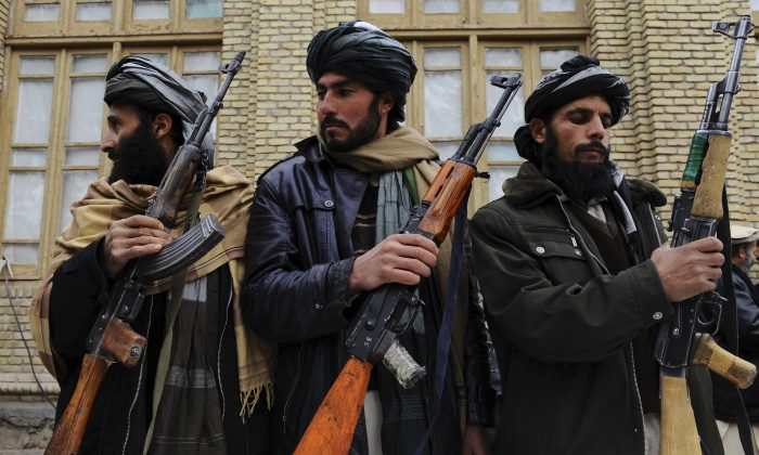 Three former Taliban fighters handover their weapons as they join a government peace and reconciliation process at a ceremony in Herat, Afghanistan, on Jan. 11, 2014.  (Aref Karimi/AFP/Getty Images)