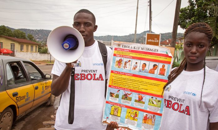 A man and woman taking part in a Ebola prevention campaign holds a placard with an Ebola prevention information message in the city of Freetown, Sierra Leone, Wednesday, Aug. 6, 2014. (AP Photo/ Michael Duff)