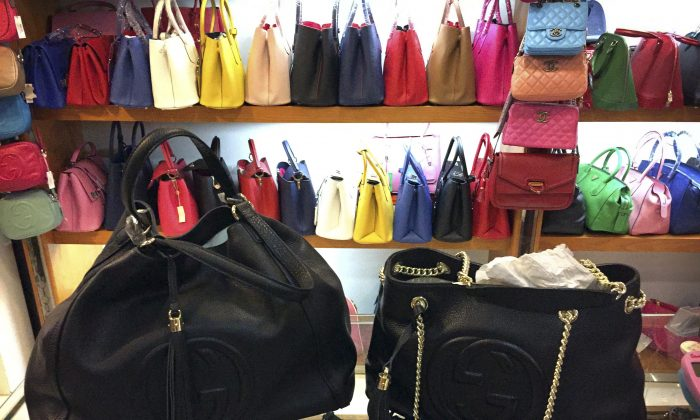 Counterfeit bags are on display in a showroom in a popular Beijing shopping mall on March 11, 2015. China's economy will need to focus on innovation instead of counterfeiting in order to grow, says Zhang Weiying.  (AP Photo/Mark Schiefelbein)
