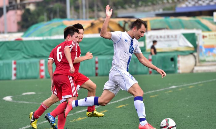 Lucky Mile's Niall Cox (white) attacks the Wanchai defence during their 3-2 win in the HKFA Division 1 match at Happy Valley on Sunday May 3. (Bill Cox/Epoch Times)
