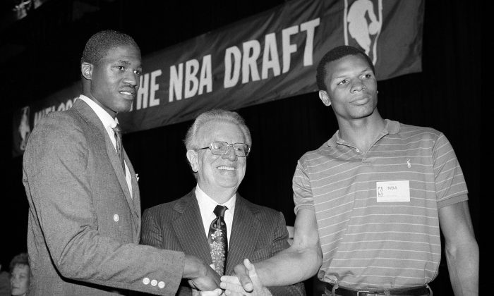 Dominique Wilkins, left, of the University of Georgia and Terry Cummings, right, of the DePaul University, join National Basketball Association Commissioner Larry O'Brien Tuesday, June 29, 1982 in New York after they were chosen in the NBA Draft. Wilkins, the third pick overall, went to the Utah Jazz and Cummings, the second pick in the first round of the draft, will go to the San Diego Clippers. (AP Photo/Marty Lederhandler)