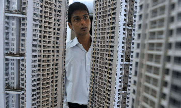 Indian sales executive looks at a model of an luxury apartment complex on a construction site of an apartment tower in Mumbai on August 9, 2010. (Punit Paranjpe/AFP/Getty Images)
