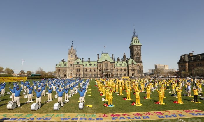 Falun Dafa practitioners, including members of the Tian Guo Marching Band and waist drum team, do their gentle exercise on Parliament Hill in Ottawa on May 6, 2015, to mark World Falun Dafa Day. Some 15 MPs from all national parties and a senator gave speeches of support and encouragement to the practitioners gathered on the Hill for the event, which drew about 600 people. (Epoch Times)