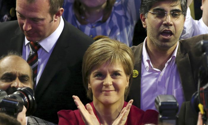 First Minister of Scotland and Scottish National Party leader Nicola Sturgeon, center, celebrates with the results for her party at the count of Glasgow constituencies for the general election in Glasgow, Scotland, Friday, May 8, 2015. (AP/Scott Heppell)