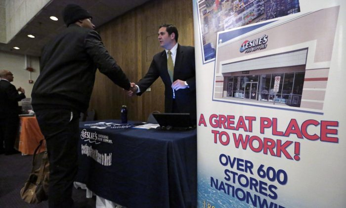 In this April 22, 2015 photo, a sign at a recruiting station for Leslie's Pool supplies boasts that it is a great place to work during a National Career Fairs job fair, in Chicago. (AP Photo/M. Spencer Green)