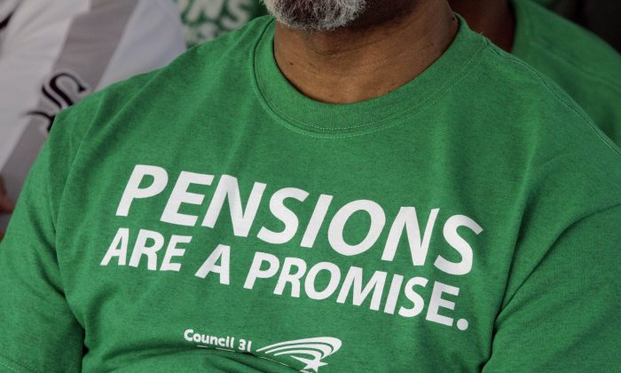American Federation of State County and Municipal Employees union members wear there protest message on their shirts while rallying against the proposed pension legislation outside the at the Illinois State Capitol Springfield, Ill. (AP Photo/Seth Perlman)