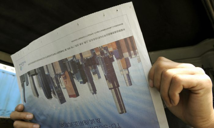 A man reads a newspaper featuring the skyscrapers in Beijing April 24, 2008. (LIU JIN/AFP/Getty Images)
