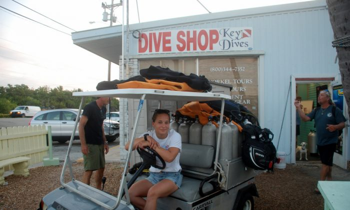 Key Dives divemaster Samantha Schuff with golf cart loaded with divers gear. Key Dives labels and takes gear from the shop to the dive boat and sets it up. (John Christopher Fine copyright 2015)