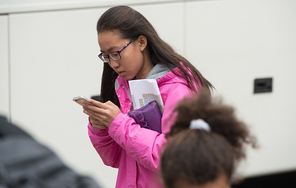 A teenager looks at her smartphone outside the Natural History Museum in Washington on April 8, 2015. (NICHOLAS KAMM/AFP/Getty Images)