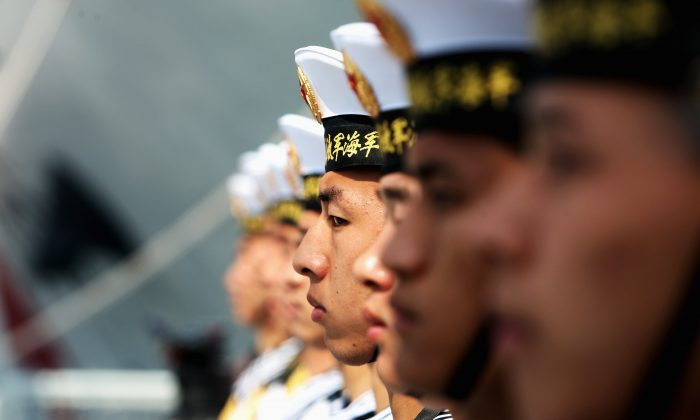 Members of the Chinese regime's People's Liberation Army Navy stand guard on a Navy Battleship of Wenzhou at Qingdao Port on April 22, 2009, in Qingdao of Shandong Province, China. The Chinese regime has deployed a new warship allegedly equipped with supersonic missiles. (Guang Niu/Pool/Getty Images)