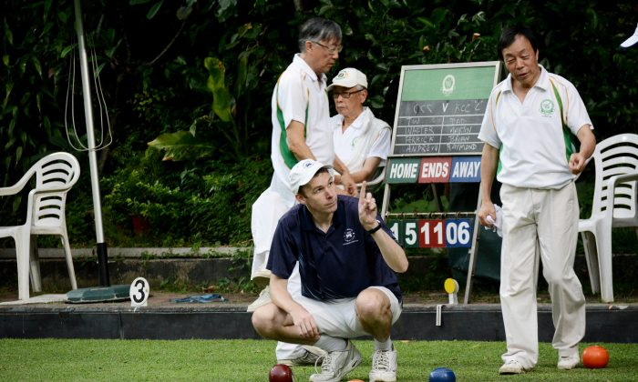 Derek Wyllie of Hong Kong Football Club indicates to his Craigengower Cricket Club opponent that his team has won a shot in this end. His rink continues the momentum and won the game 19:9, contributing to the overall victory of 5-3 away from home at CCC on Saturday May 9, 2015. (Stephanie Worth)