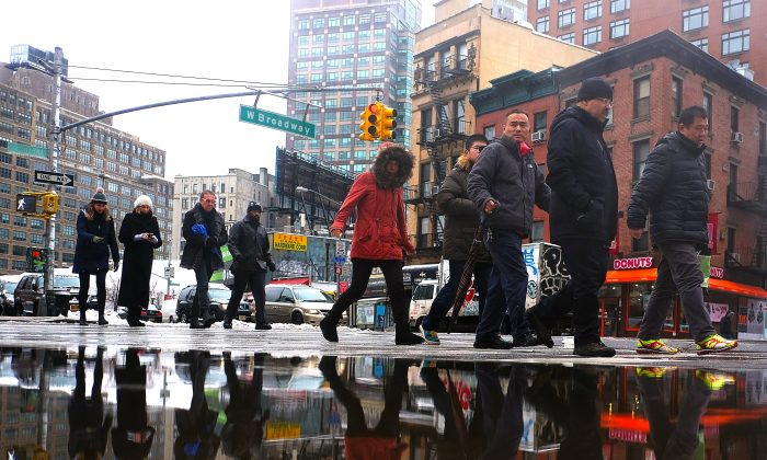 People walk by a puddle made by melted snow on a street in New York,  Feb. 2, 2015. ( Jewel  Samad/AFP/Getty Images)
