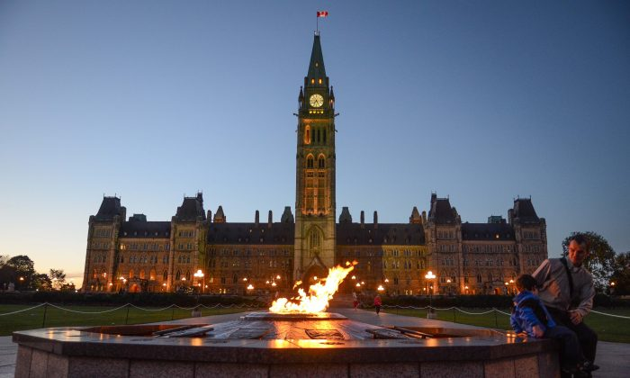 Visitors look at the Centennial Flame on Parliament Hill. Canadians can expect to see multiple federal election debates during this campaign season as part of a major upheaval in the way the leaders square off in person. (Matthew Little/Epoch Times)
