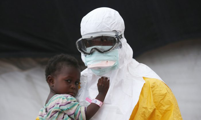 A Doctors Without Borders (MSF), health worker in protective clothing holds a child suspected of having Ebola in the MSF treatment center on October 5, 2014 in Paynesville, Liberia. (John Moore/Getty Images)