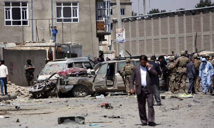 U.S. and Afghan security forces inspect the site of suicide attack near an international airport in Kabul, Afghanistan, Sunday, May 17, 2015.  (AP Photo/Rahmat Gul)