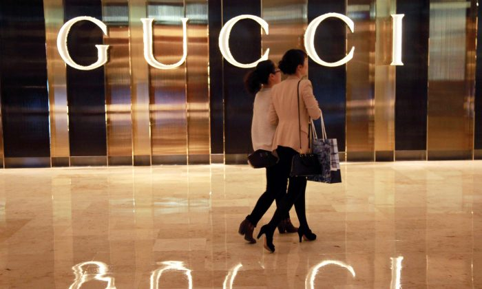 Chinese shoppers walking past a Gucci shop in Nanjing, east China's Jiangsu province.  (STR/AFP/Getty Images)