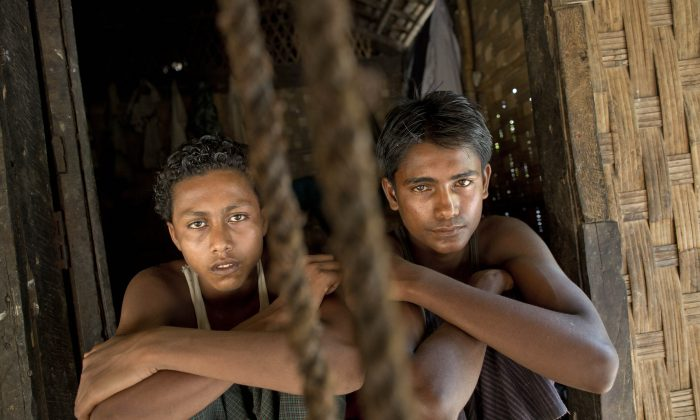 In this Monday, May 11, 2015, photo 16-year-old Sadik Hussein, left, and 17-year-old Noor Alam, hours after returning to their homes in Thetkabyin Village, north of Sittwe, western Rakhine state, Myanmar.  (AP Photo/Gemunu Amarasinghe)