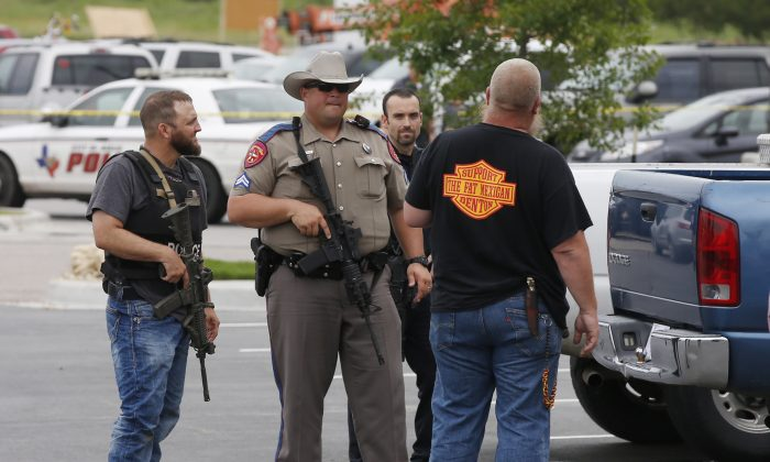 """Law enforcement officers talk to a man near the parking lot of a Twin Peaks Restaurant Sunday, May 17, 2015, in Waco, Texas, after a shooting involving rival biker gangs. Waco police Sgt. W. Patrick Swanton told KWTX-TV there were """"multiple victims"""" after gunfire erupted between the gang members. (Rod Aydelotte/Waco Tribune Herald via AP)"""