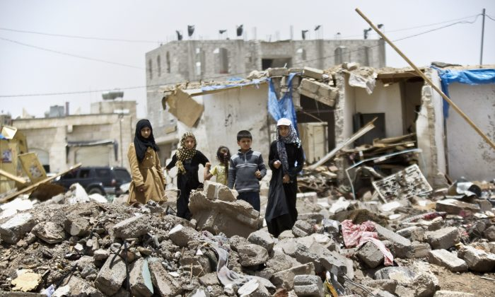 A boy and his sisters watch graffiti artists spray on a wall, commemorating the victims who were killed in Saudi-led coalition airstrikes in Sanaa, Yemen, Monday, May 18, 2015. (AP Photo/Hani Mohammed)