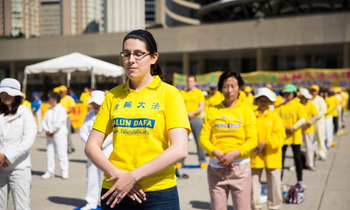 A young woman practices Falun Dafa exercises on Nathan Phillips Square, May 17.(Evan Ning/Epoch Times)
