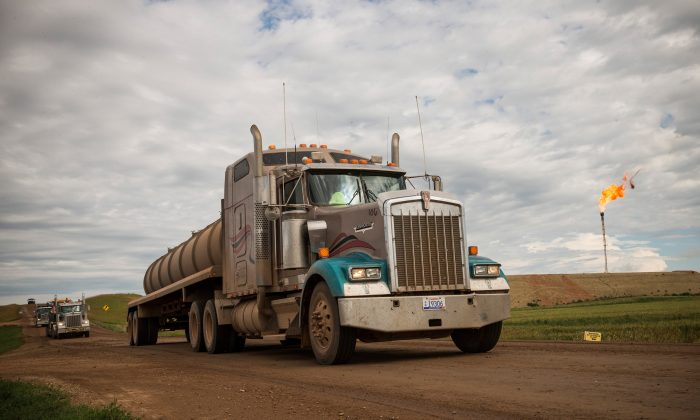 A line of trucks drives past a gas flareoutside Watford City, N.D., on July 23, 2013.  (Andrew Burton/Getty Images)
