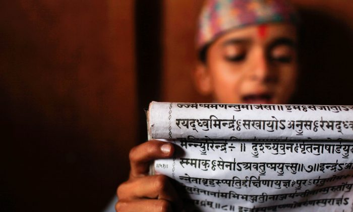 A young student reads Sanskrit scripts while attending class at Budhanilkantha Vedh Vidhya ashram, a school imparting vedic knowledge  in Katmandu, Nepal, on June 13, 2013.  (AP Photo/Niranjan Shrestha)