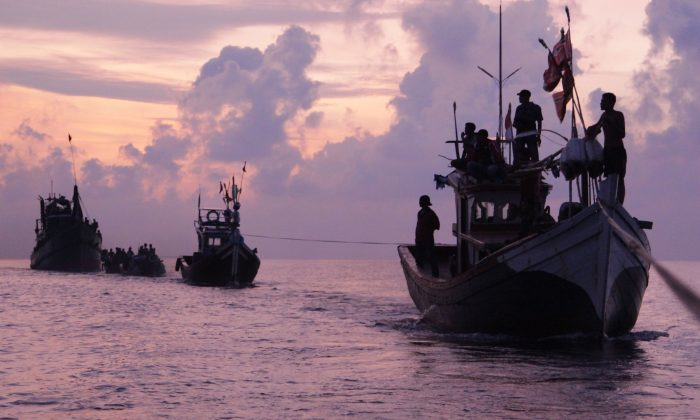 Acehnese fishermen are silhouetted by the rising sun as they rescue migrants who are stranded on their boat on the sea off East Aceh, Indonesia, Wednesday, May 20, 2015. (AP Photo/S. Yulinnas)