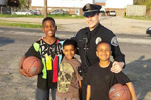 Camden police officer with youth. (Courtesy of COPS/U.S. Department of Justice)